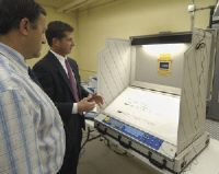 Mike McMahon<BR>Larry Bugbee, left, Republican Rensselaer County Board of Elections commissioner, looks on while Robert Witko, president of Liberty, demonstrates an electronic voting machine that will be used in Tuesday's school board election in Troy.